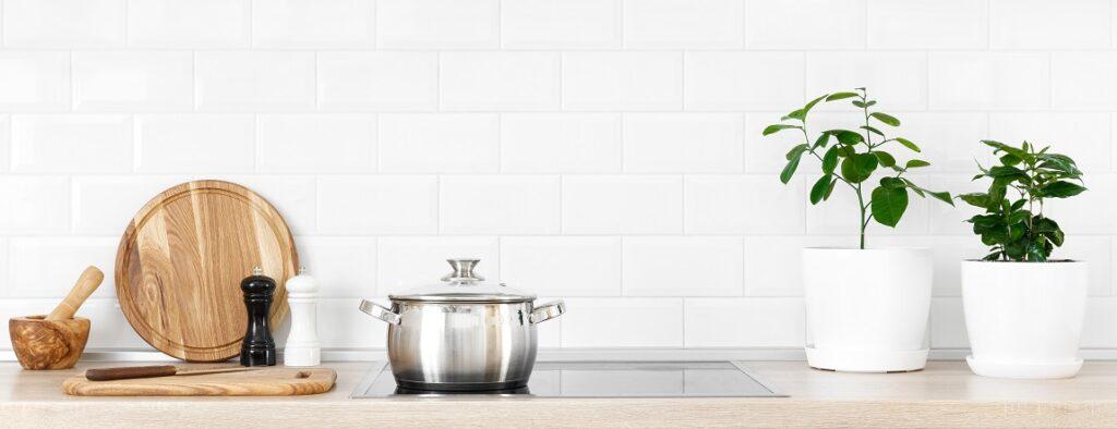 White modern kitchen interior with wooden worktop and kitchenware, culinary concept, background, banner